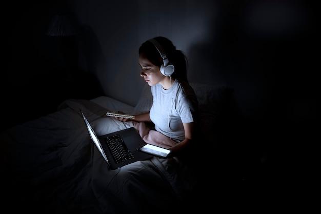 Mujer con auriculares trabajando hasta tarde en casa