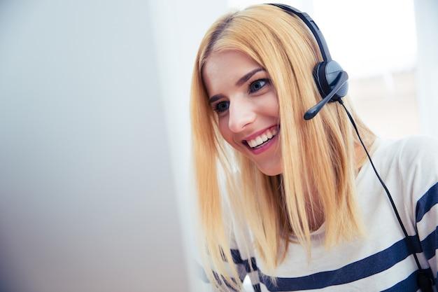 Mujer en auriculares usando computadora de escritorio
