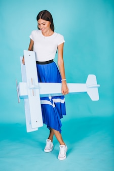 Mujer con avión de juguete sobre fondo azul