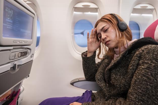 Mujer en avión sufre de mareo con dolor de cabeza de estrés en el tiempo de vuelo.