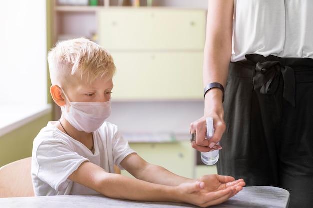 Mujer ayudando a un estudiante a desinfectar sus manos