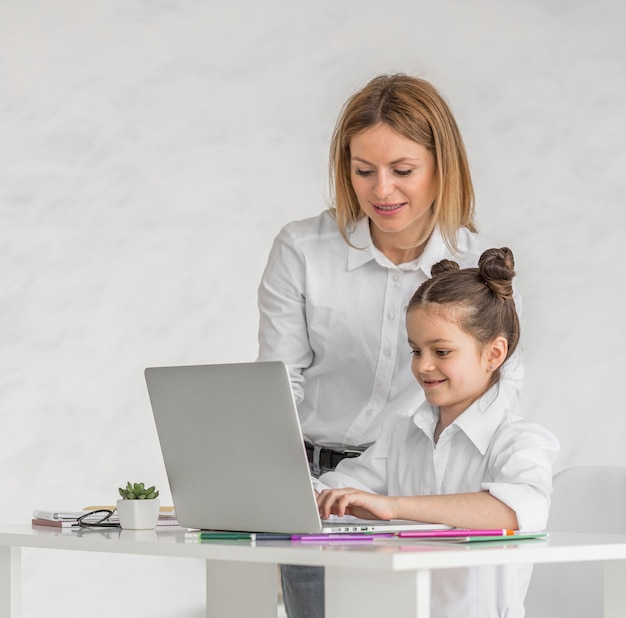 Mujer ayudando a su hija mientras toma una clase en línea