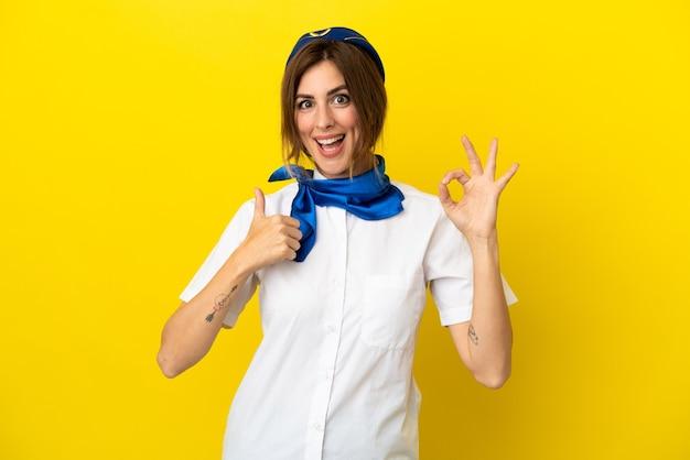 Mujer de azafata de avión aislada sobre fondo amarillo que muestra el signo de ok y el pulgar hacia arriba gesto