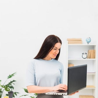 Mujer en azul escribiendo en el teclado del ordenador portátil