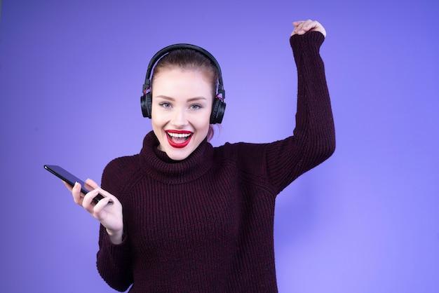 Mujer baila con auriculares en la cabeza y teléfono móvil en la mano