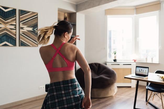 Mujer bailando en casa siguiendo lecciones en video en la computadora portátil