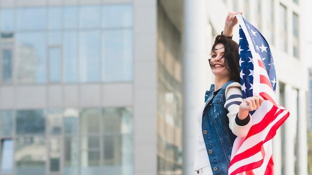 Mujer con bandera americana en calle de la ciudad