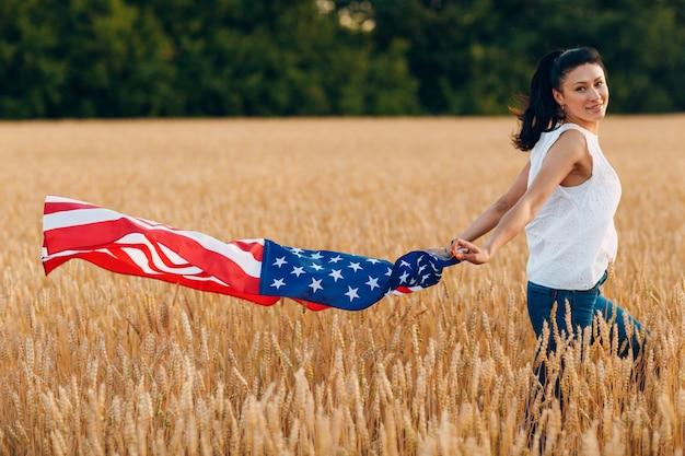 Mujer con bandera americana en campo de trigo al atardecer