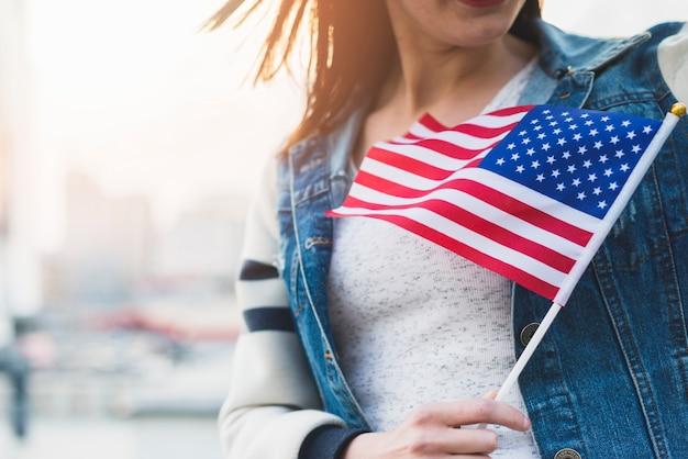 Mujer con bandera americana en palo en mano