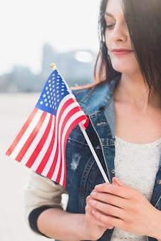 Mujer con bandera estadounidense en el exterior el cuatro de julio.