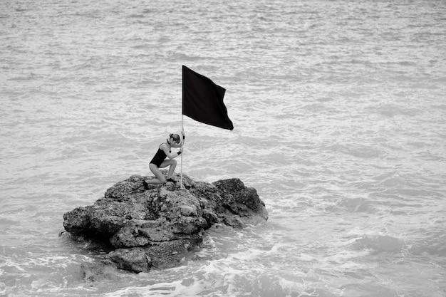 Mujer con una bandera en una roca