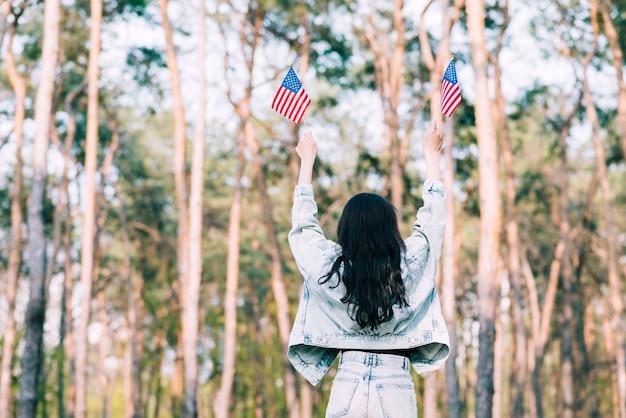 Mujer con banderas de estados unidos en manos extendidas.