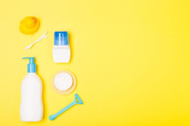 Mujer baño limpieza cuidado mañana rutina vista superior composición plana endecha con blanco, azul amarillo artículos en escritorio amarillo.