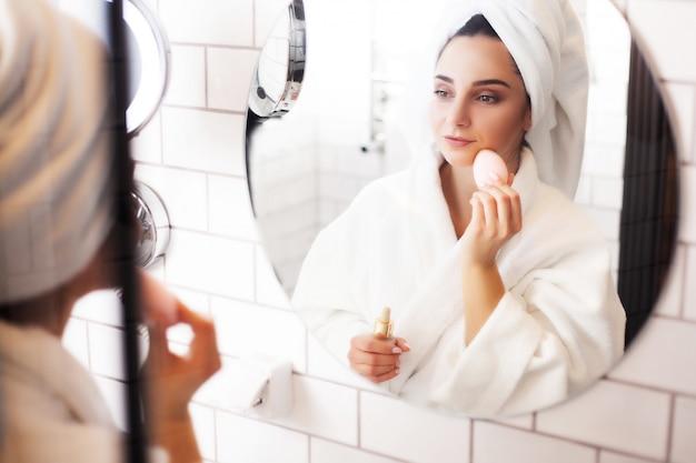 Mujer en el baño con una toalla sobre su cabeza aplica maquillaje en su rostro