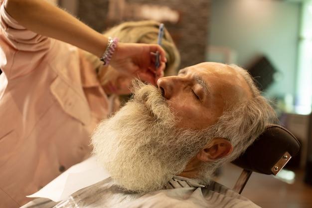 Mujer barbero afeitarse la barba de un cliente en una barbería.