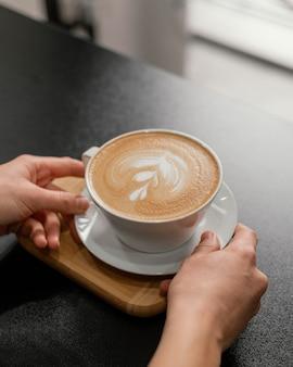 Mujer barista colocando una taza de café decorada en el mostrador