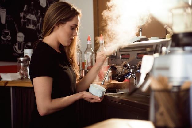 Mujer barista haciendo café en el mostrador de la cafetería. barista mujer trabajando en cafe
