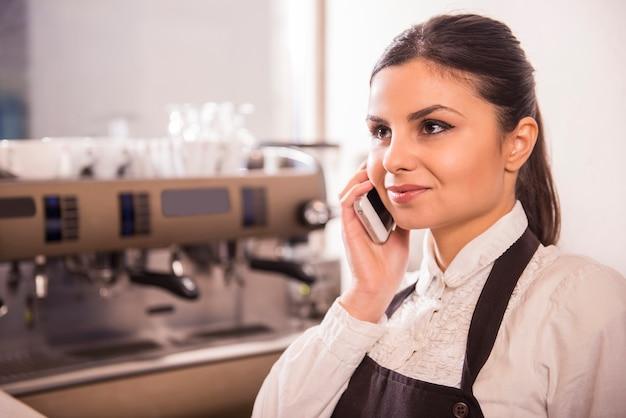 La mujer barista está tomando órdenes por teléfono.