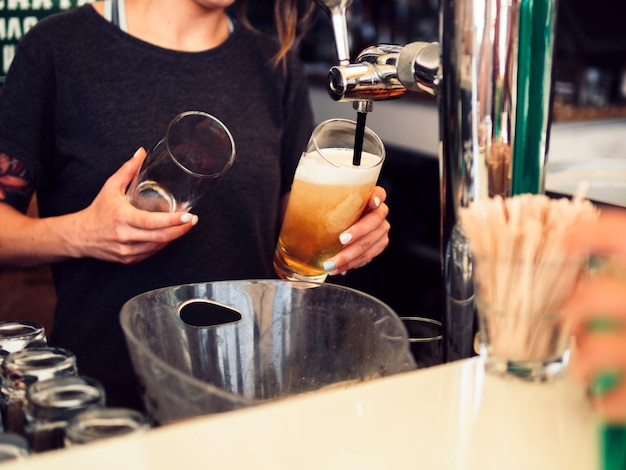 Mujer barman vertiendo cerveza