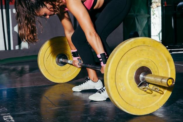 Mujer con barra de pesas amarilla en gimnasio