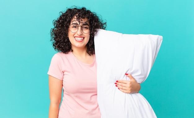 Mujer bastante árabe que parece feliz y gratamente sorprendida. en pijama y sosteniendo una almohada