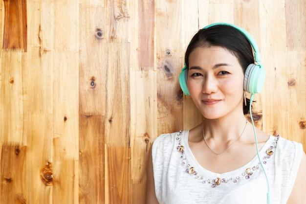 Mujer bastante asiática con los auriculares que sonríe y que mira a través de cámara.