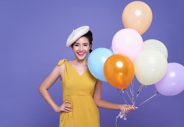 Mujer bastante asiática en la fiesta de celebración con globo colorido.
