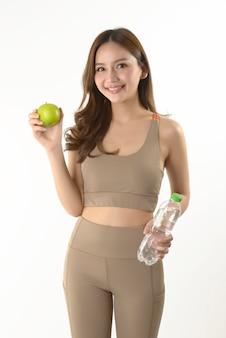 Mujer bastante asiática con manzana y agua