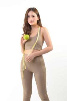Mujer bastante asiática con manzana y cinta métrica en blanco