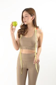 Mujer bastante asiática con manzana y cinta métrica
