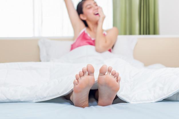 Mujer bastante asiática que despierta y que bosteza en su cama en el dormitorio