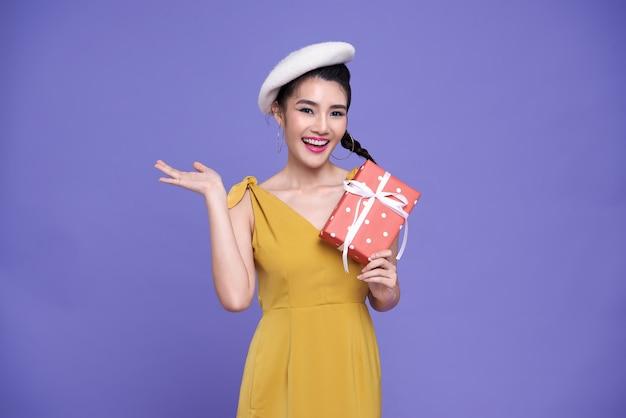 Mujer bastante asiática con regalos rojos.