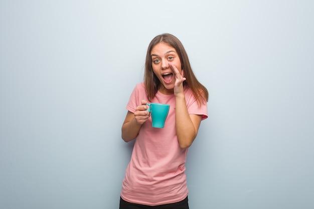 Mujer bastante caucásica joven que grita algo feliz al frente. ella sostiene una taza.