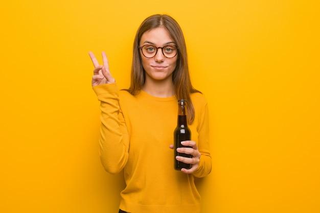 Mujer bastante caucásica joven que muestra el número dos. ella está sosteniendo una cerveza.