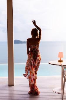 Mujer bastante caucásica en vuelo vestido de verano en el restaurante de la villa del hotel de lujo de vacaciones