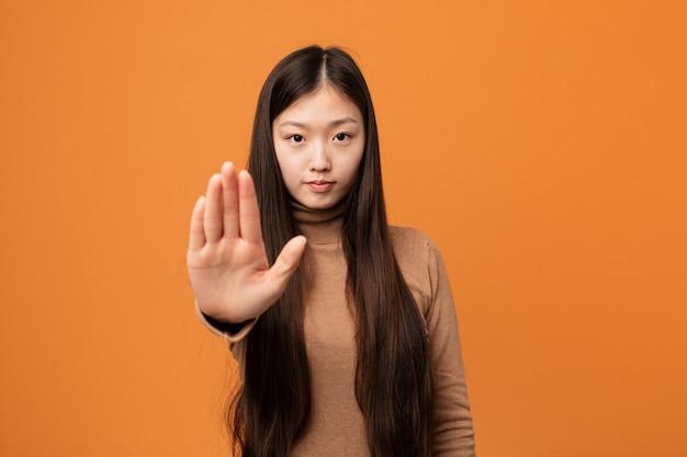 Mujer bastante china joven que se coloca con la mano extendida que muestra la muestra de la parada, previniéndole.