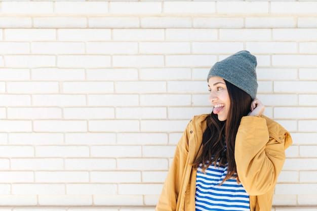 Mujer bastante feliz que se pega la lengua delante de la pared de ladrillo