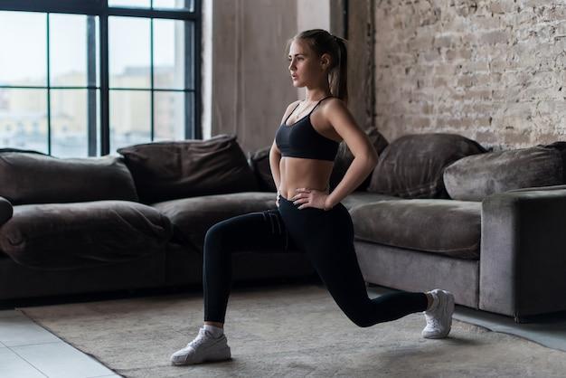Mujer bastante en forma haciendo estocadas frontales o ejercicio en cuclillas en interiores en un piso