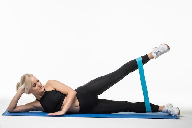 Mujer bastante fuerte haciendo ejercicios de estiramiento en el suelo en el estudio en blanco