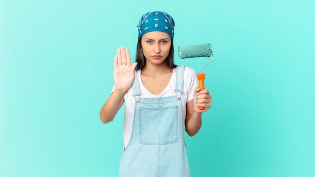 Mujer bastante hispana que parece seria que muestra la palma abierta que hace gesto de la parada. concepto de casa de pintura