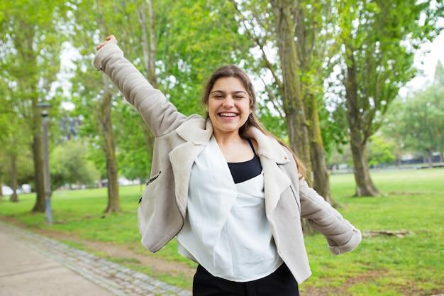 Mujer bastante joven alegre que separa los brazos en parque