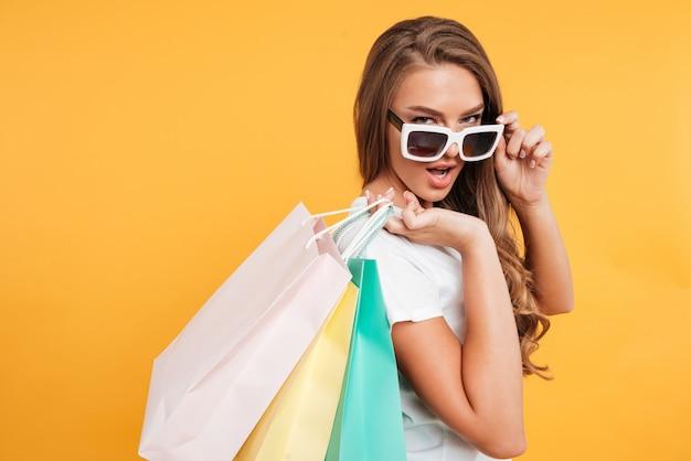 Mujer bastante joven asombrosa que sostiene bolsos de compras.