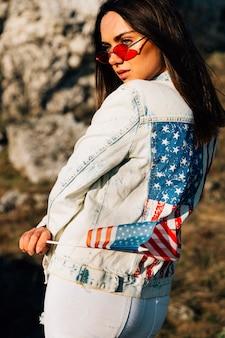 Mujer bastante joven en chaqueta del dril de algodón con la bandera americana en día asoleado
