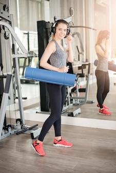 La mujer bastante joven del deporte es entrenamiento con la estera en gimnasio