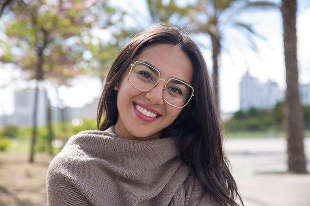 Mujer bastante joven feliz que presenta en la cámara en parque de la ciudad