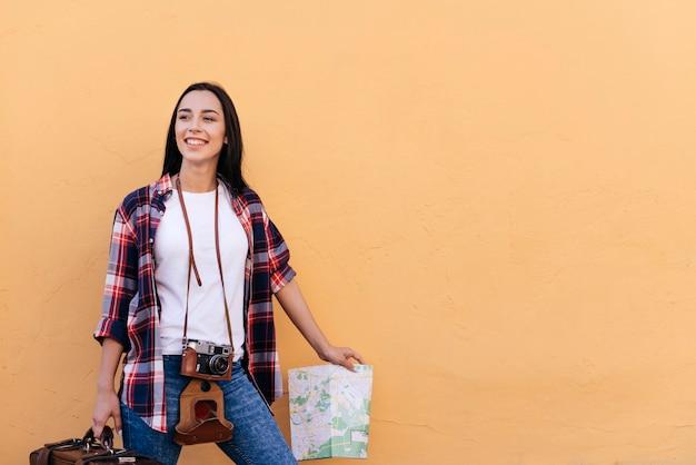 Mujer bastante joven feliz que sostiene el bolso y el mapa que se colocan cerca de la pared del melocotón