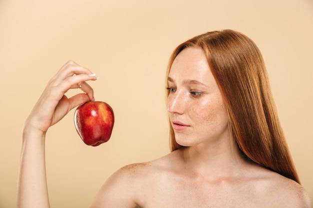 Mujer bastante joven del pelirrojo que sostiene la manzana que mira a un lado.