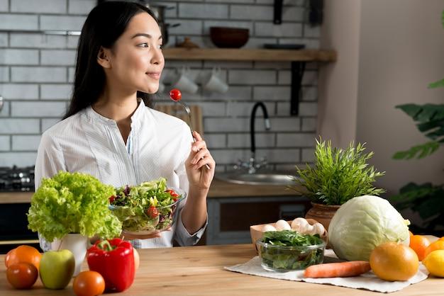 Mujer bastante joven que come el tomate de cereza rojo que sostiene el cuenco de ensalada mezclada