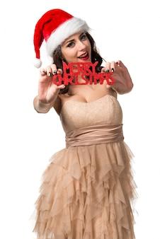 Mujer bastante joven que lleva a cabo letras de la feliz navidad. concepto de navidad
