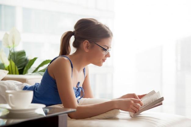 Mujer bastante joven que se relaja en el sofá con el libro